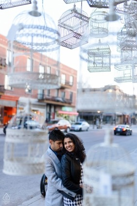 Engaged couple's portrait surrounded by suspended bird cages - Engaged couple's portrait surrounded by suspended bird cages