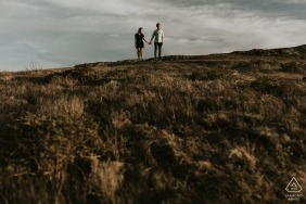 Engagement portrait of a couple holding hands in the San Francisco hills