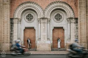 portrait de fiançailles de sai gon représentant un couple debout dans des ouvertures séparées lorsque les scooters passent