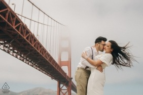 San Francisco engagement portrait session at the Golden gate Bridge   the wind blows her hair as the fog obscures the bridge
