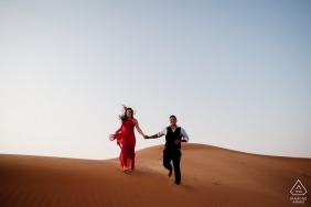 Maleiha Desert, Dubai engagement portrait session - Desert adventure in the sand with a red dress