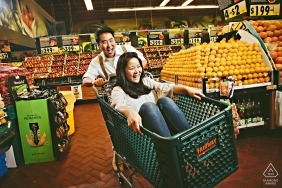 Fairway Market engagement portraits - Couple having fun in a supermarket with a shopping cart basket