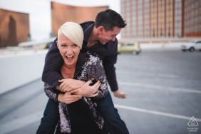 Las Vegas engagement portraits at the hotel parking lot   Let's Ride - she gives him a piggyback ride in the city