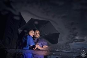 St Katherine's Dock, UK engagement portraits with rain and shared umbrella