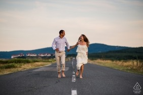 Engagement portraits in Sozopol, Bulgaria - Running couple right down the middle-of-the-road