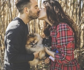 Engagement shoot of a young couple in love in Carrara, holding two small dogs as they kiss.