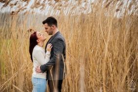 Verlobungsporträt eines Paares, das sich hält, während sie in hohen Gräsern in Delapré Abbey, Northampton stehen.