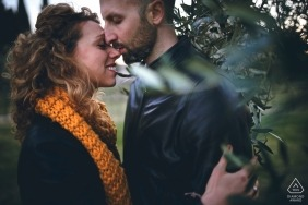 A sweet engagement photo of a couple standing together among greenery in Assisi, Italy.