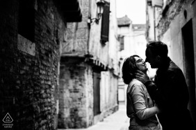 Black and white engagement photo of a couple about to kiss in a narrow street surrounded by old stone buildings in Agen, France.