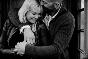 Zwart en wit verlovingsportret van een paar knuffelen en glimlachen in Epe.