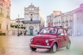 Engagement photo of a couple driving in a small red car through Siracusa.