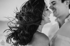 Black and white engagement portrait with wind blowing through the bride's hair in Plataforma de Osório.