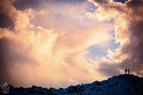 Photo d'engagement d'un couple debout au sommet d'une colline enneigée au lever du soleil, entouré de nuages d'orage en Islande.