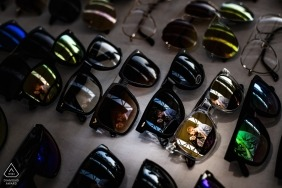 Engagement photo of a couple reflected in lenses at a sunglasses stand in Reggio Calabria.