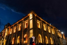 Engagement portrait of a couple standing in front of a stone building lit up at night in Reggio Calabria.