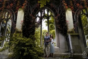 Engagement portrait of a couple standing arm in arm in front of St. Dunstan in London.