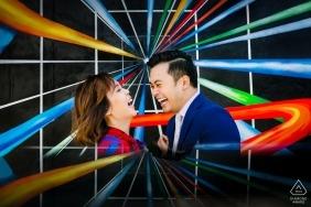 Verlobungsporträt eines Paarlachens umgeben durch vibrierende, grafische Farben in Venedig, Kalifornien.