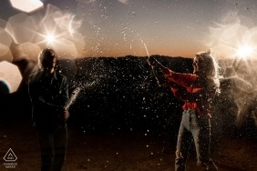 Glendale, AZ Lit Engagement PhotoShoot at Night with a couple popping champagne