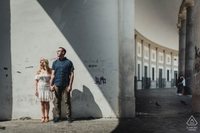 Couple holds hands while looking off into the distance in this Piazza del Plebiscito Napoli engagement photography session