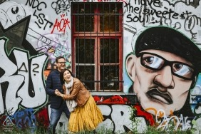 Engagement portrait shoot captured couple laughing in front of a serious looking gravity man as captured in Ljubljana