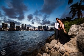 Casal posar nas rochas ao lado do oceano, enquanto o horizonte de Miami está à distância nesta sessão de fotos de noivado
