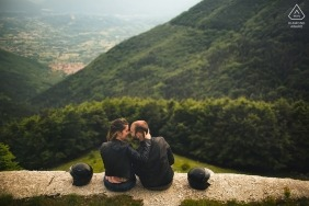 Parco Nazionale d'Abruzzo engagement photo shoot as the couple sits on a ledge overlooking a forest below
