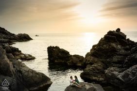 Calabre - le couple se prélasse sur un grand rocher au bord de l'océan alors que le soleil se couche derrière eux lors de cette séance photo de fiançailles