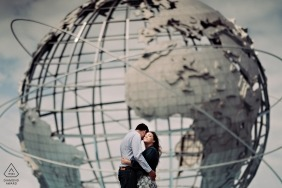 During this engagement shoot, a couple hugs in front of a large world sculpture in Flushing Meadows park