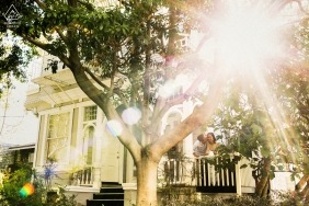 This image of a couple kissing on the front porch while the sun shines through the trees was captured in a San Francisco engagement photo session