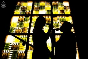 The silhouettes of the couple sipping wine in front of a green and brown stained glass window was created during a San Francisco engagement photo shoot