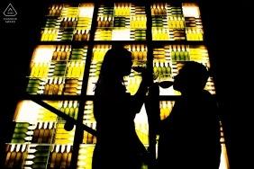 在旧金山订婚照片拍摄期间,在绿色和棕色彩色玻璃窗前啜饮葡萄酒的夫妇的剪影