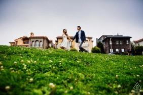 San Francisco Engagement Fotografie - Paar hält die Hände, als sie durch einen grasbewachsenen Hof schlendern