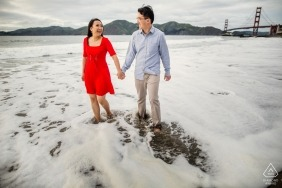 San Francisco Engagement photo session - woman in a bright red dress holds hands with her future husband as they stand in the tide on the beach