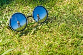 Fuijan - we can see the reflection of the couple kissing in a pair of glasses resting on the grass in this pre-wedding portrait session