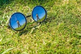 Fuijan - on peut voir le reflet du couple s'embrasser dans une paire de lunettes posée sur l'herbe lors de cette séance de portrait précédant le mariage