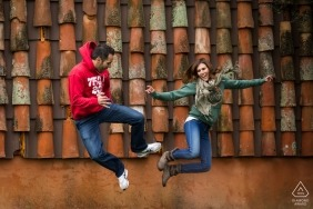 Jumping engaged couple portrait in a front roof at Toledo, Castilla-La Mancha (Spain)