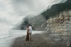 Se ve a la pareja tomados de la mano en una playa cubierta de piedras, en esta sesión de fotos de compromiso de Nápoles.