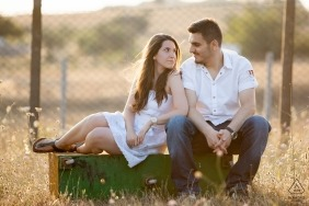 Silivri, İstanbul Engagement Portrait of a couple sitting on a flipped-over metal box in front of a fence and looking at each other