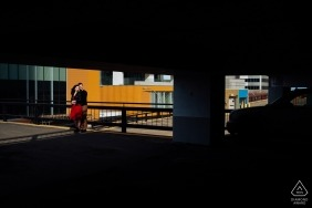 Edmonton, AB engagement photo session- couple smile in the sun outside of a multi-level parking garage