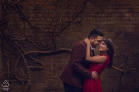 London, UK engagement PhotoShoot- couple smile happily at each other in front of a vine covered brick wall