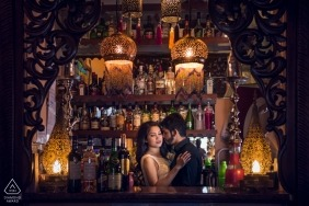 Bath, UK engagement photo session of a couple embracing in front of a well stocked bar