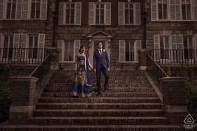 London, UK engagement photo session. Couple stands holding hands on stone steps leading up to a large gray building