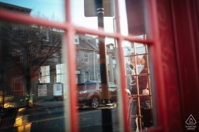 Baltimore, Maryland engagement photo shoot - Couple kisses next to an old phone booth