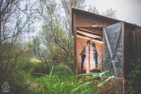 La mariée se tient debout sur des caisses et s'embrasse dans une petite hutte lors de la séance photo de fiançailles à Priolo, réalisée par un photographe sicilien.