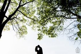 A couple is silhouetted as they stand beneath trees on a bright, sunny day in this engagement photo by a Zhejiang, China photographer.