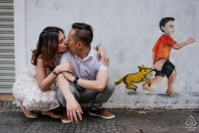 A couple squats on the ground kissing in front of a wall in Ho Chi Minh with graffiti art of a boy and a dog in this engagement photo by a Vietnam photographer.
