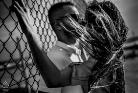 A woman's hair blows in the wind in Cabo de Gata as she and her fiance stand against a fence in this black and white pre-wedding photo by a Murcia, Spain photographer.