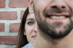 A woman peeks out from behind her fiance in this pre-wedding portrait in Milan, Italy. Taken by a Lombardy photographer.