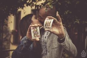 Ein Paar hält eine Königin der Herzen und einen König der Herzen hoch, während sie sich während ihrer Hochzeitssitzung durch einen Ligurien-Fotografen unter einem Baum in Bolano küssen.