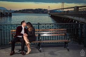 Dieses Foto wurde während der Dämmerung nahe Pier 14 in San Francisco gemacht. Es ist ein beliebter Ort für Einheimische und Touristen, die sich glücklich schätzen, ein schnelles Foto mit dem Paar zusammen zu machen.